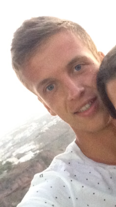 Smiling blonde man wearing a white polka-dotted t-shirt. There is part of a woman's forehead that has been cropped out of the photo next to his left cheek. Standing outside behind a scenic background during the day time.
