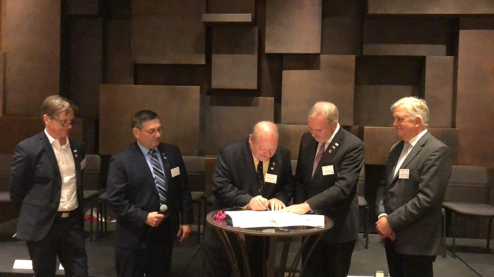 Photo of the signing of the second and perpetual Climate Protection Partner Agreement with representatives from the City of Morris and the City of Saerbeck, Germany.