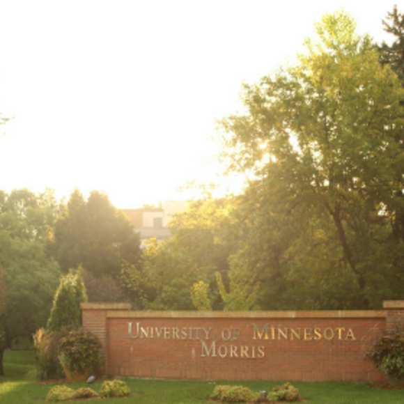 The 4th Street entrance to the UMN Morris campus, with the sun coming up behind it