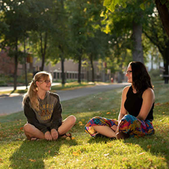 Two students smile at each other on a sunny fall evening on the campus mall.