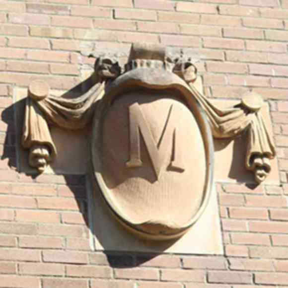 A stylized letter M on the facade of a brick building