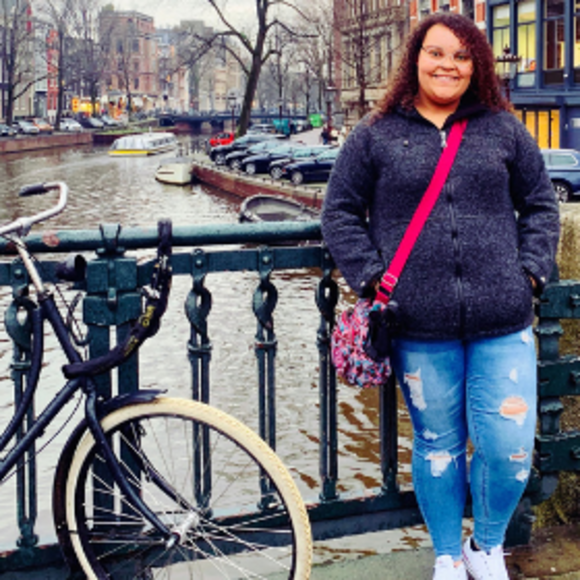 Maya Bledsoe standing on a bridge, next to a bicycle, colorful houses in the background