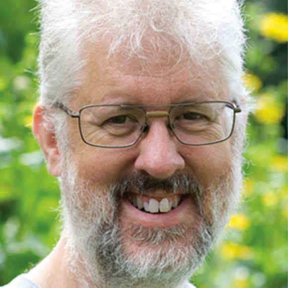 Man with short white hair and glasses smiles into lens.