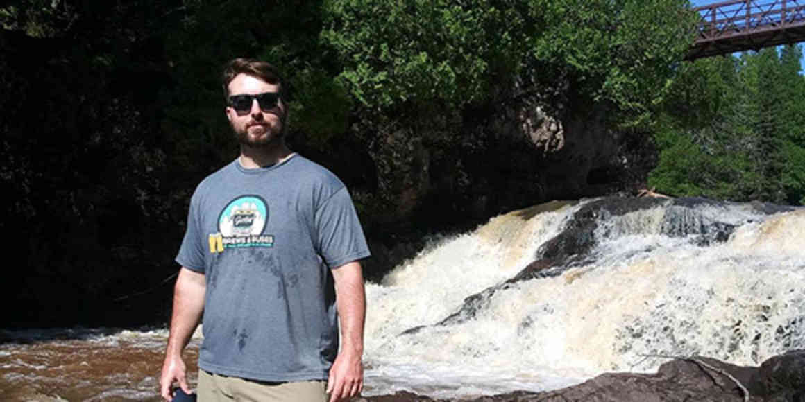 Young man with short dark hair and beard, wearing sunglasses, poses in front of a waterfall and green summer leaves.