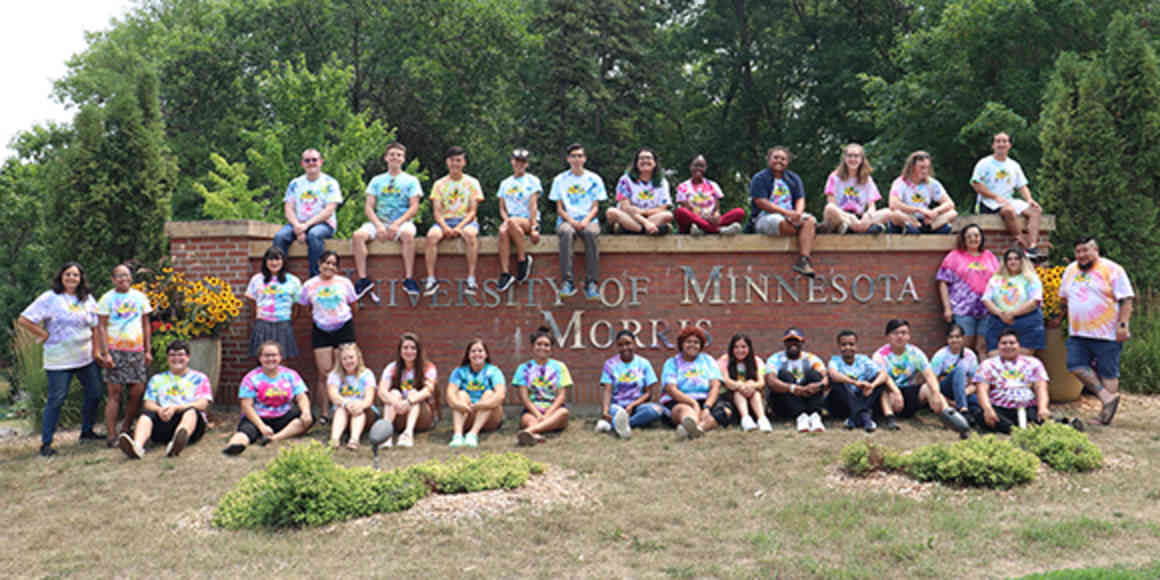 A group of students and staff wearing tie-dyed t-shirts poses on and around the campus entrance sign.