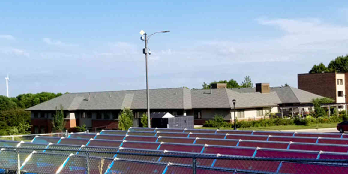 The Green Prairie Community on a sunny summer afternoon. Solar panels fill the immediate foreground, and a wind turbine is in the far distance. The building is new construction, stucco and brick with a hip roof.