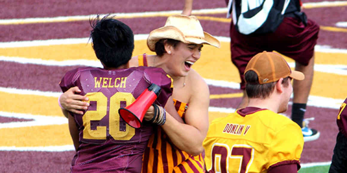 Students in festive UMN Morris gear celebrate with the football team on the field after the Homecoming game