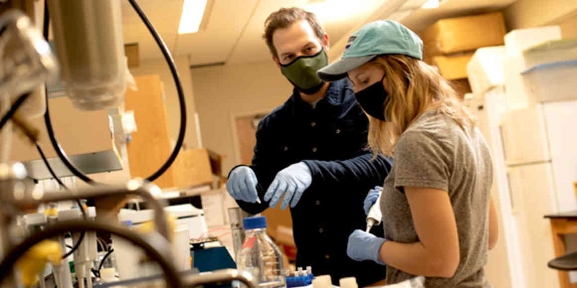 A faculty person explains a lab process to a student in a science lab, surrounded by scientific equipment.