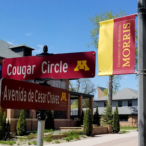 """Street signs mark """"Cougar Circle"""" and """"Avenida de Cesar Chavez,"""" a banner declares, """"University of Minnesota Morris,"""" and campus buildings bask in warm spring sunshine."""