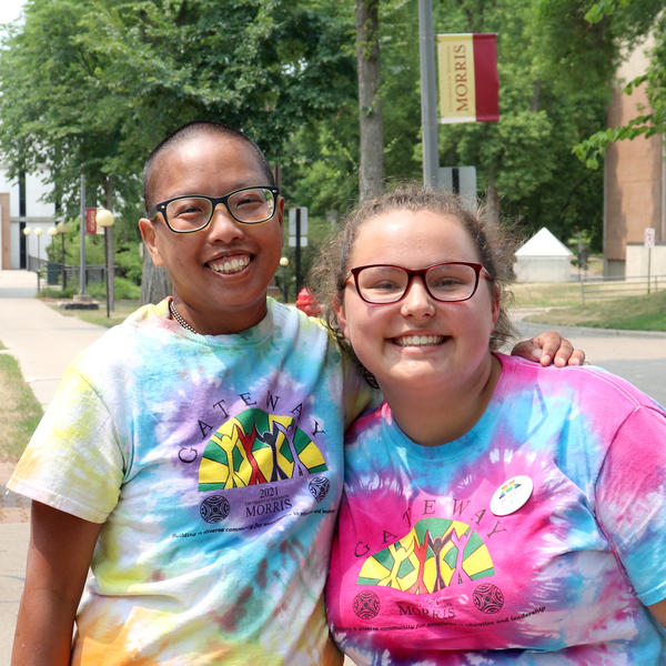 A student and a staff mentor wearing tie-dyed t-shirts smile into lens.