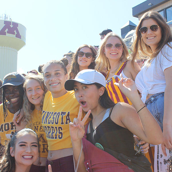 A group of students in maroon and gold at the football stadium